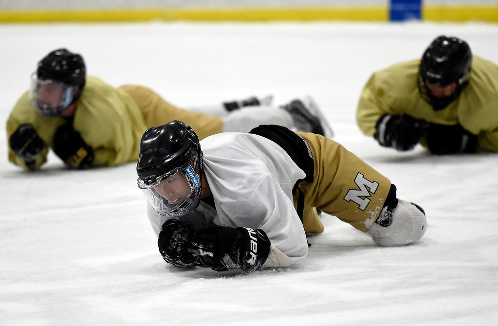 . SUPERIOR, CO - NOVEMBER 28, 2018: Monarch High School hockey player Andrew Kim and other do the army crawl across the ice during practice on Wednesday at the Sports Stable in Superior. More photos: BoCoPreps.com Jeremy Papasso/ Staff Photographer