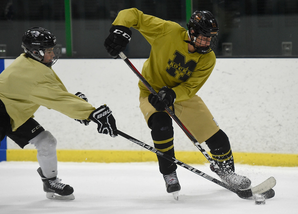 . SUPERIOR, CO - NOVEMBER 28, 2018: Monarch High School hockey player Zack Given, at right, moves the puck towards the goal during practice on Wednesday at the Sports Stable in Superior. More photos: BoCoPreps.com Jeremy Papasso/ Staff Photographer
