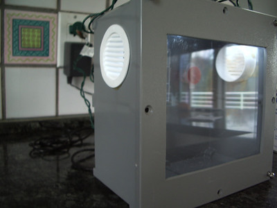I got a 8x8x4 electric junction box at Home Depot. Cut out a window and covered with plexiglass. Put some roof vents in the side, pill box feeder inside along with cotton ball  holder. Put some LED Christmas lights in the top that are on a timer.  Also put a piece of balsa wood on the top. It wasn't cheap, but it's way cool! I will use it every year when we do our Monarch project! Photo 1 of 2, submitted by Scott D.