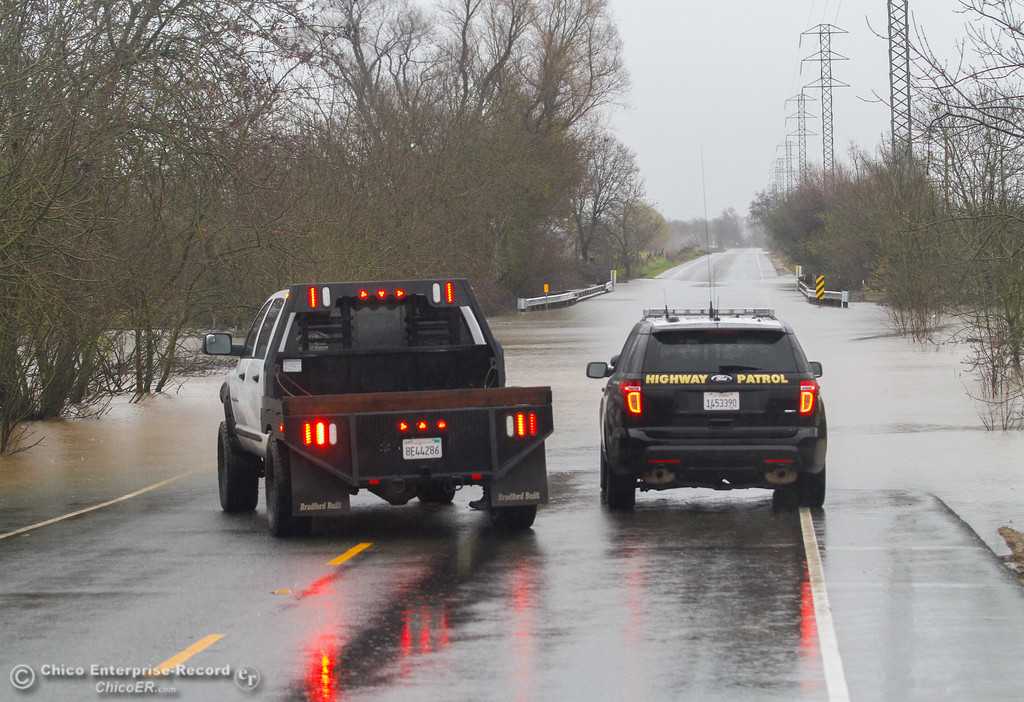 . A truck and California Highway Patrol vehicle stop at a flooded section of Lower Honcut Road February 20, 2017 in Oroville, California. (Emily Bertolino -- Mercury Register)