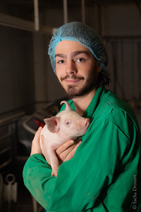portrait of a model holding a piglet