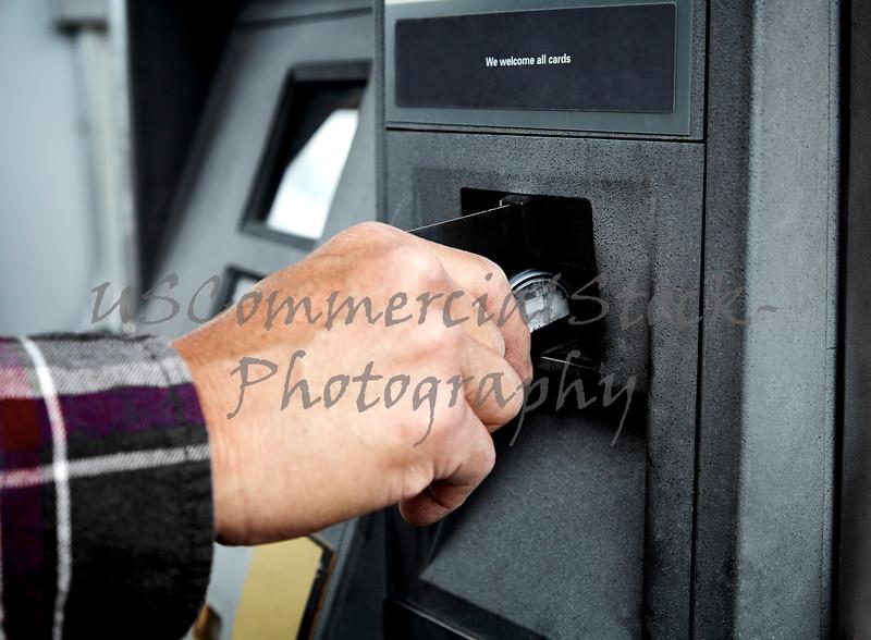 Mans Hand putting a Debit Card n an ATM Machine
