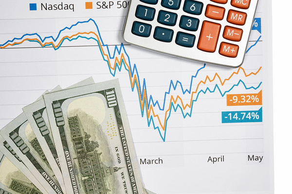 Stock Market Graph with One Hundred Dollar Bills and a Calculator