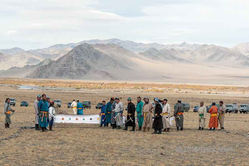 Competitors watching an arrow fly towards to target (best larger to find the arrow in the air), Eagle Festival, Olgii, Western Mongolia