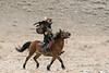 Eagle hunter galloping with his golden eagle, Eagle Festival, Olgii, Western Mongolia
