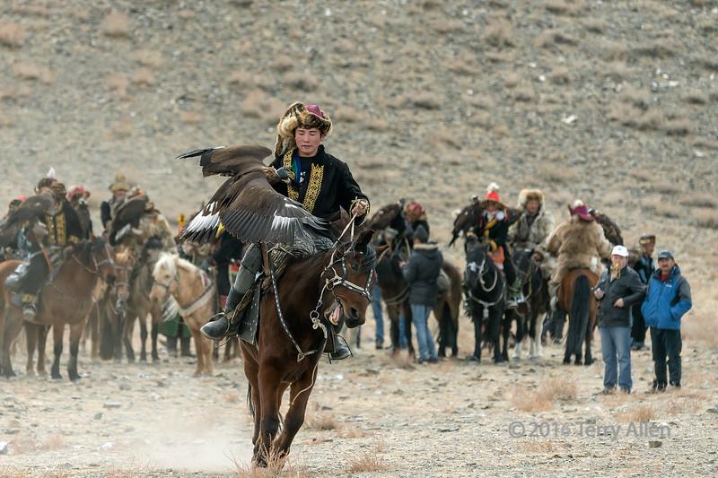Young eagle hunter riding towards the judges, Eagle Festival, Olgii, Western Mongolia