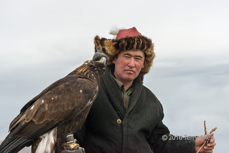 """Portrait of a hunter with his golden eagle<br /> <br /> One of the competitors at the Eagle Festival, Olgii, Western Mongolia.  <br /> <br /> For other images of the start of the compeition, including one of a 'parked' eagle, see here: <a href=""""http://goo.gl/TCN4xr"""">http://goo.gl/TCN4xr</a><br /> <br /> 30/05/15  <a href=""""http://www.allenfotowild.com"""">http://www.allenfotowild.com</a>"""