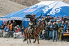 Young eagle hunter riding by the judges to the right of the image, Eagle Festival, Olgii, Western Mongolia