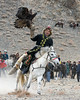 Competitor riding fast with golden eagle and fox skin, Eagle Festival, Olgii, Western Mongolia<br /> <br /> Best eagle, costume and horse harness competition.