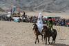 Young couple in wedding attire on horseback, Eagle Festival, Olgii, Western Mongolia