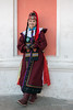 Woman-in-ethnic-attire-outside-the-Soviet-era-theater,-Khovd,-Western-Mongolia