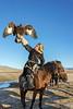 Kazakh eagle hunter holding his eagle high, Western Mongolia