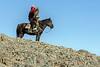 Kazakh eagle hunter and eagle on a hill top, Western Mongolia