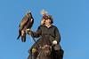 Elder eagle hunter bracing his heavy eagle on a specially designed crutch, Western Mongolia
