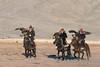 Three Kazakh tribesmen riding with their golden eagles at sunrise, Western Mongolia