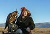 Kazakh eagle hunter holding his golden eagle, Western Mongolia