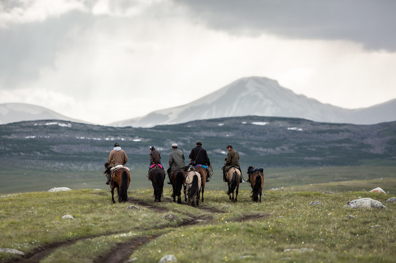 Four men, one boy riding horseback away from the camera towards the mountains, Altai Mountains, Mongolia