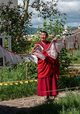 Monk hanging prayer flags