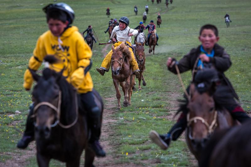 Kids racing horses towards the camera, Altai Mountains, Mongolia
