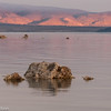 The first rays of the rising sun hit the mountains behind Mono Lake.