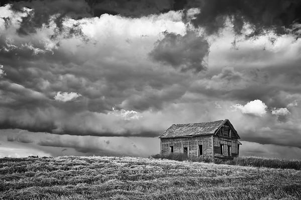 An abandoned farmhouse under a threatening autumn sky