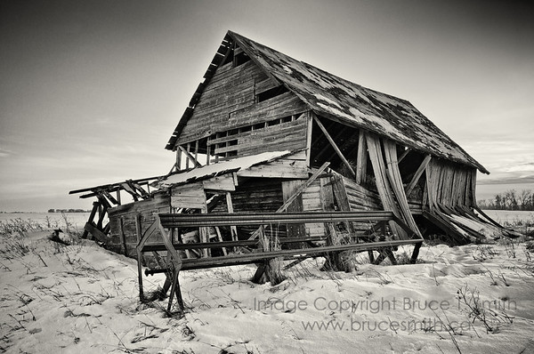 Abandoned farm building and combine blade - monochrome