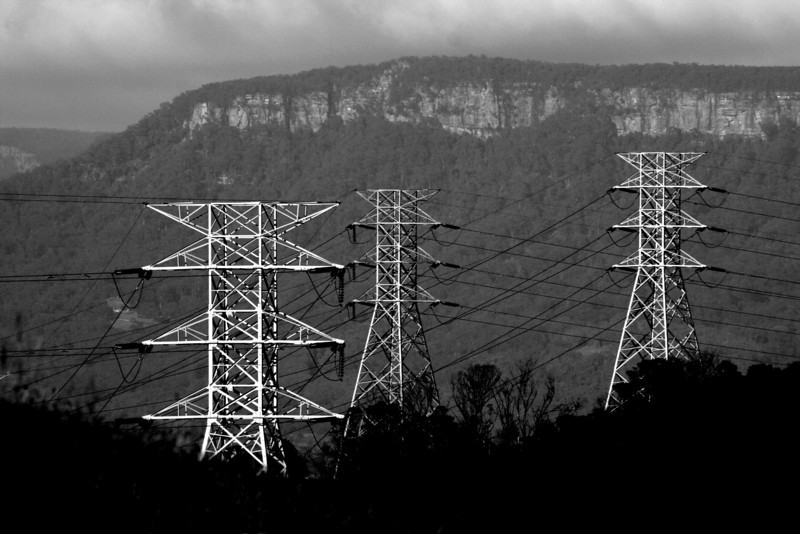 The dramatic mountain scenery of the Illawarra Escarpment dominates the landscape behind a trio  of electricty pylons. View from the southern Wollongong suburb of Berkeley.