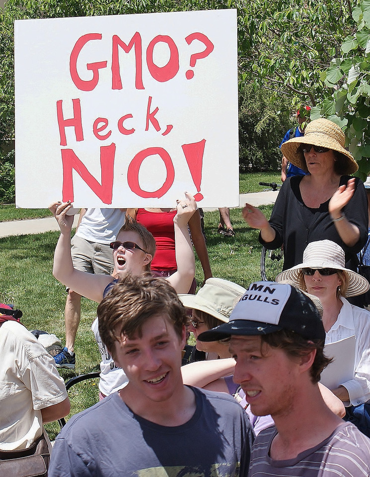 Woman shouts while holding ant-GMO sign.