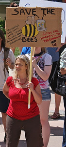Woman holding sign about bees and GMOs.
