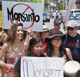 Young women in protest march, anti-Monsanto sign in background.