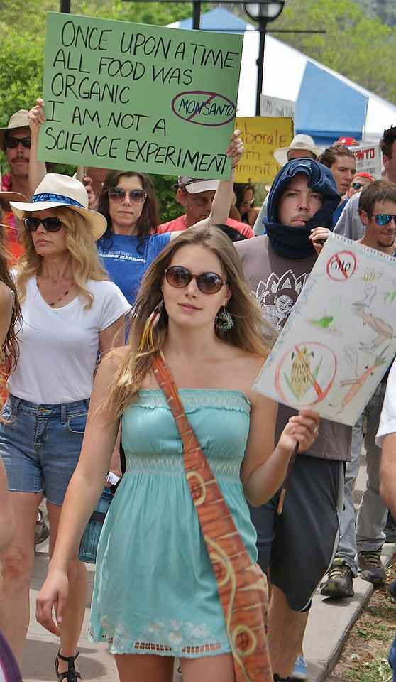 Protester with sign about organic food, other anti-GMO demonstrators marching.