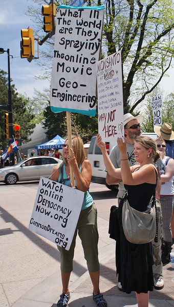 Two women holds signs against Monsanto and geo-engineering, other protesters behind them.