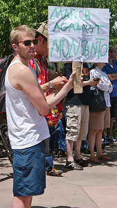 Young man with sunglasses with march against Monsanto sign.