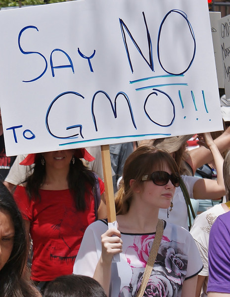 Young woman marching with ant-GMO sign, other protesters behind her.