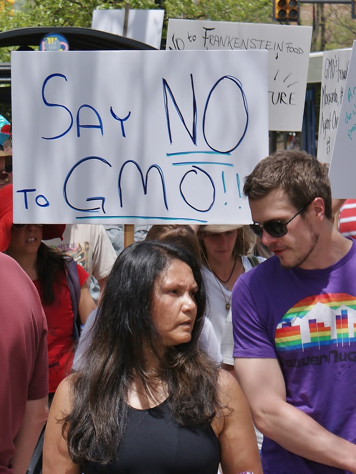 Man and woman marching in protest, anti-GMO sign behind them.