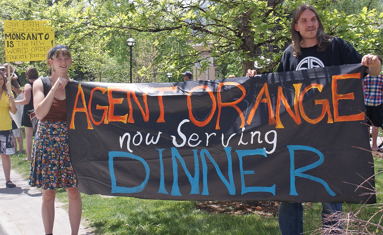 Two demonstrators hold sign about agent orange at GMO protest.