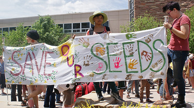 "Young women holding sign, ""Save Our Seeds""."