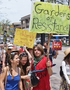 Group of young protesters with signs about gardening and seeds.