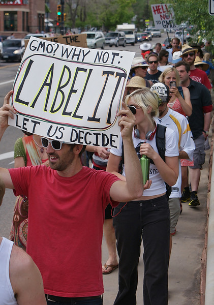 Man in protest march with sign about GMO labeling.