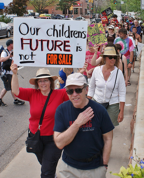 "Woman raises about ""our childrens future"", line of marchers in background."