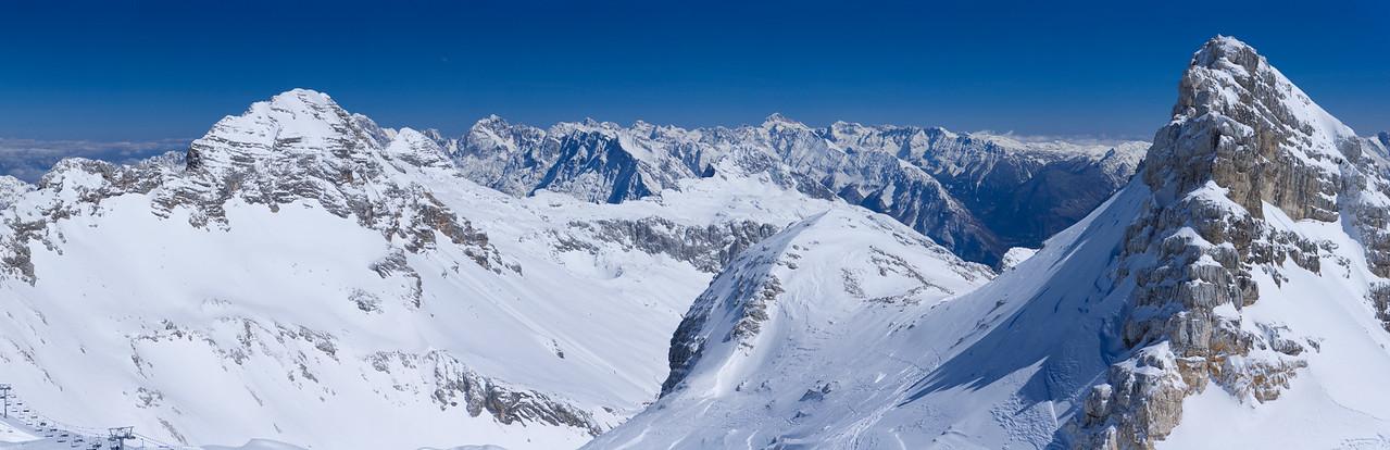 Qui siamo sulle pendici del Monte Forato / Prestreljenik. Al sinistra il Monte Leupa.  In lontananza si sviluppano le Alpi Giulie orientali, di cui Jalovec a sinistra e Tricorno / Triglav a destra sono le due vette più evidenti, ed anche le più alte, in questa immagine.  Foto Claudio Costerni n. 070406-555062