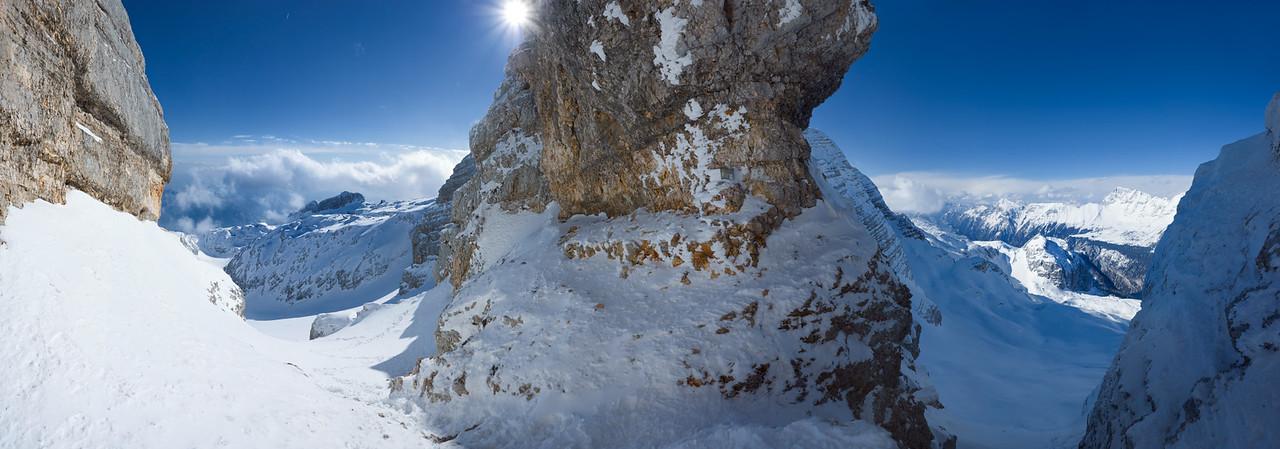 """Qui siamo nel foro del Monte Forato con lo sguardo verso ovest - Gruppo del Canin - Alpi Giulie. Sulla sinistra del """"pilastro"""" centrale che è una parte della parete interna, ad arco, del foro, c'è il versante sud, ed a destra il versante nord del gruppo del Canin. A sinistra la Slovenia, a destra l'Italia. In lontananza, sulla destra, separato dalla Val Raccolana, si intravvede il Montasio e parte del suo altopiano.  Foto Claudio Costerni n. 010306-983040"""