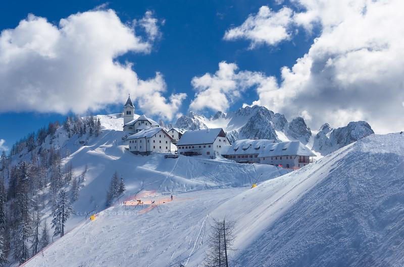 """Alpi Giulie <br /> Monte Lussari 110306-1303c <br /> Borgo del Lussari e parte iniziale (a monte) della pista di discesa Di Prampero. <br /> Si vede il monte Lussari, dietro il campanile del Santuario e la Cima Cacciatore (con forma ad anfiteatro) dietro le casette.<br /> <br /> <a href=""""http://www.promotur.org/code/14939/La-localita"""">http://www.promotur.org/code/14939/La-localita</a>"""