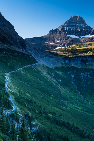 """Going-to-the-Sun Road is the only road that crosses Glacier National Park in Montana, USA, going over the Continental Divide at Logan Pass. It was completed in 1932. A fleet of 1930s red tour buses called """"jammers"""" which were rebuilt in 2001 to run on propane or gasoline, offer tours on the road. The road, a National Historic Landmark and a Historic Civil Engineering Landmark, spans 53 miles (85 km) across the width of the park.<br /> <br /> The road is one of the most difficult roads in North America to snowplow in the spring. Up to 80 feet (24 m) of snow can lie on top of Logan Pass, and more just east of the pass where the deepest snowfield has long been referred to as Big Drift. The road takes about ten weeks to plow, even with equipment that can move 4000 tons of snow in an hour. The snowplow crew can clear as little as 500 feet (150 m) of the road per day. On the east side of the continental divide, there are few guardrails due to heavy snows and the resultant late winter avalanches that have repeatedly destroyed every protective barrier ever constructed. The road is generally open from early June to mid October, with its latest-ever opening on July 13, 2011."""