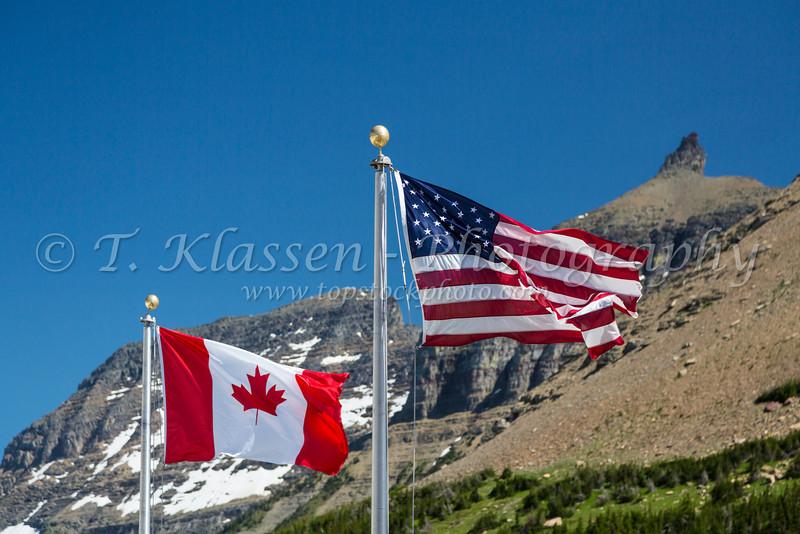 Canadian and American flags at Logan Pass, Glacier National Park, Montana, USA.