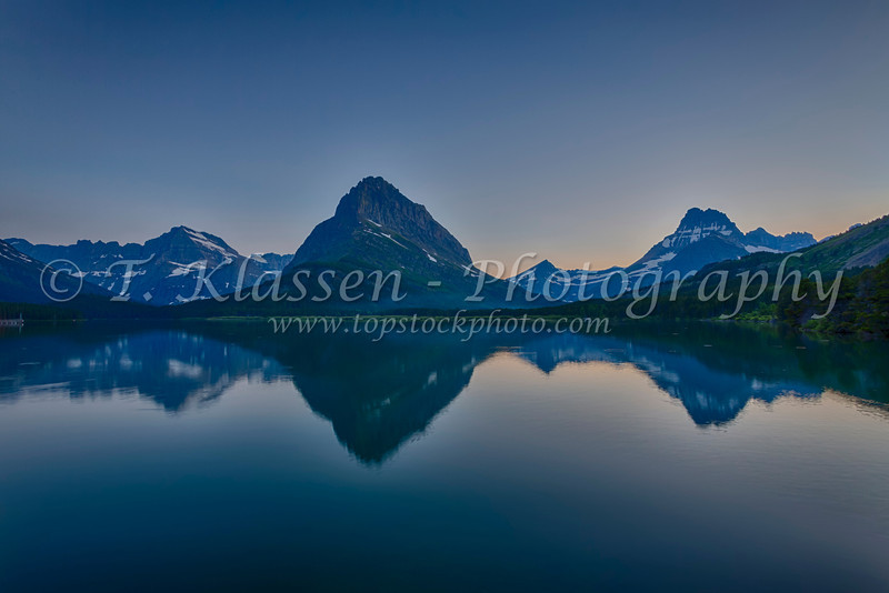 Swiftcurrent Lake and reflections of Grinnel Point and Mount Henkel at sunset in Glacier National Park, Montana, USA.