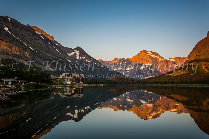 Swiftcurrent Lake and reflections of Grinnel Point and Mount Henkel at sunrise in Glacier National Park, Montana, USA.