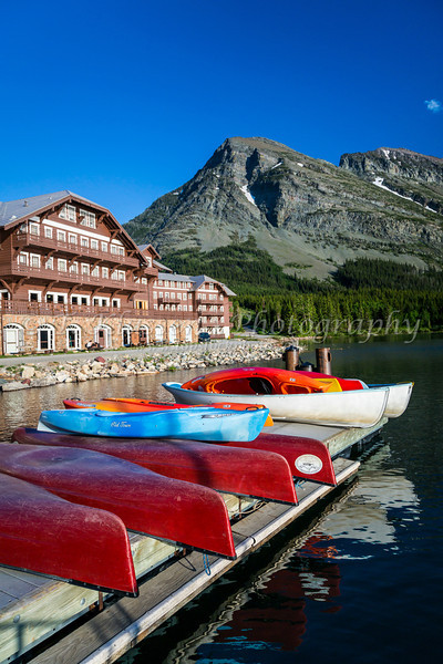Colorful canoes at the boat dock of the Many Glacier Hotel on Swiftcurrent Lake in Glacier National Park, Montana, USA.