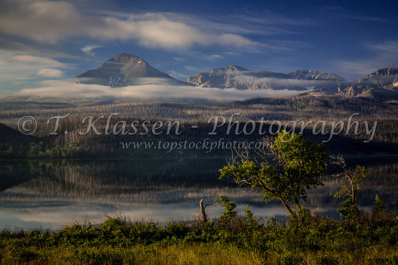 Early morning mist and reflections in St. Mary Lake in Glacier National Park, Montana, USA.