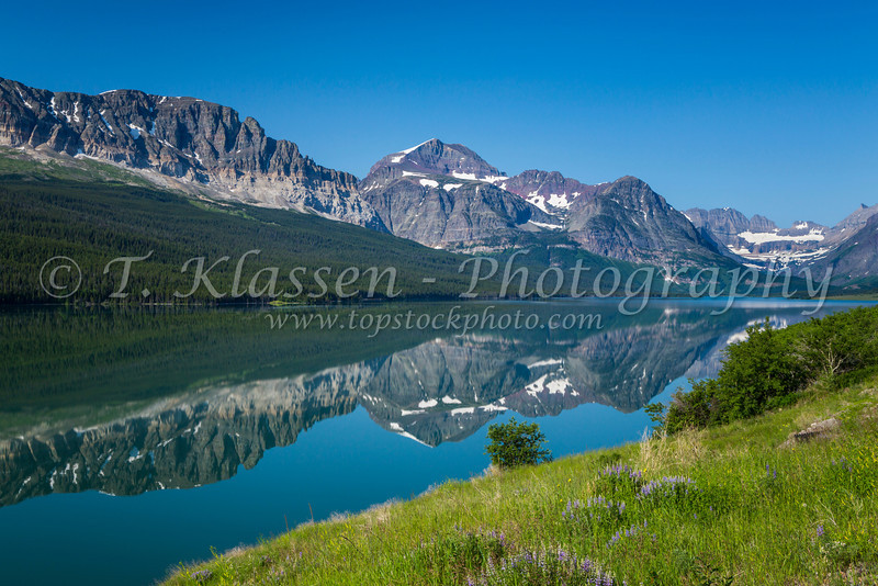 Mountain reflections in a calm Lake Sherburne in Glacier National Park, Montana, USA.